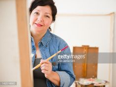 Stock-Foto : Hispanic woman painting on canvas