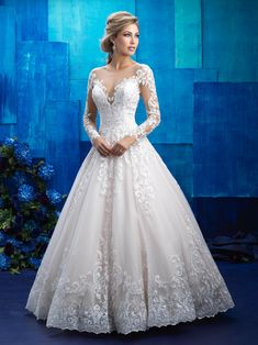 This Allure Bridals 9411 tulle wedding dress is adorned with lace appliques, with an illusion scoop neckline atop the sweetheart bodice and an illusion back. Covered buttons accent the long illusion sleeves and the full length of the back to the tip of the chapel train. The ball gown skirt cascades into a softly scalloped hemline. Available in sizes 2-32