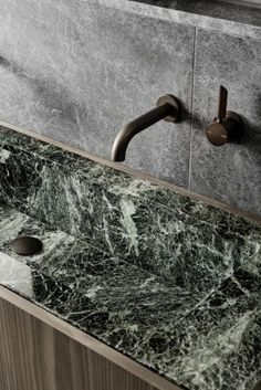 A closer view of the bathroom fittings and stone splashback and green marble sink