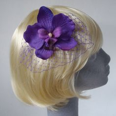 Purple fabric orchid flower with veiling on a comb.