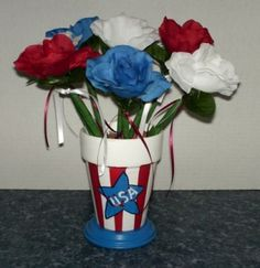 Hand painted pot painted in patriotic colors, filled with red, white & blue flower pens