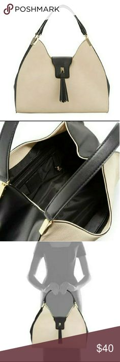 """Neiman Marcus Two Tone Tassel Hobo NWOT New and never worn. Two Tone faux leather (polyurethane)in black and cream. Two flat top handles (9"""" drop). Interior fabric lining. 9.5""""H x 15.3""""W x 5""""D Neiman Marcus Bags Hobos"""