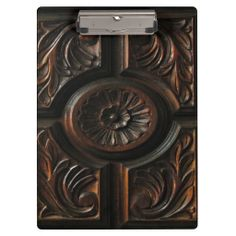 A unique clipboard for keeping all your paperwork together featuring a photograph of a wood carving with a central floral motif.