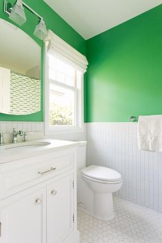 Vertical white porcelain wall tiles are fitted beneath a bright green painted upper wall, as a window dressed in a white roman shade is positioned over a white porcelain toilet fixed to white hex floor tiles. Bright Green Bathroom, Blue Green Bathrooms, Grey Bathrooms, Bathroom Colors, Beautiful Bathrooms, Green Painted Walls, Black Walls, Blue Powder Rooms, Green Powder