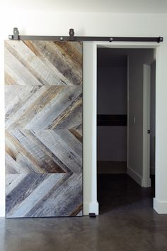 Wood panels arranged in a chevron pattern give this sliding barn door a modern appearance while also maintaining a rustic, industrial look as well.