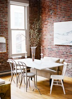 Exposed brick walls in modern dining space with mix and matched chairs