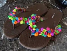 To make these, all you need is a pair of plain flip-flops and a package of water balloons. Just tie the balloons around the straps of the flip-flops, mixing the colors, until the straps are covered