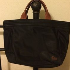 Like new Dooney black nylon tote Firm Used once briefly lightweight authentic black nylon tote w/ embroidered Dooney duck, has Dooney & Bourke genuine serial number tag. Beautiful construction, looks new. Absolutely no marks! Hot pink interior w/traditional phone pocket, a large full length center dividing pocket, 4 slip pockets & one back wall zippered pocket. Extremely roomy!!! Magnetic close snap, molded leather handles. Hand or arm carry, not intended for wearing as a shoulder bag…