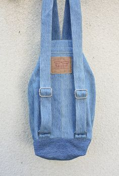 a durable, large capacity denim backpack, washable and multipurpose- use it for a shopping day in town, as a beach bag, a gym bag, a school bag (a hardcover A4 folder fits comfortably inside) or even a nappy bag. made from Levi jeans in excellent condition.  * strong adjustable straps, handmade from 100% cotton denim that feels soft on skin  * full lining with 2 inner pockets, one with YKK zipper  color: light blue jeans  height - 47cm/18.5 bottom- 19cm*19cm/7.5*7.5 (square) strap length…