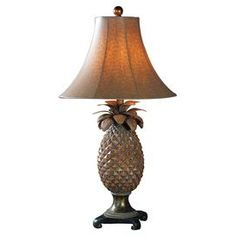 Evoking breezy tropical locales, this artful table lamp showcases a hand-rubbed pineapple base accented by a brown ostrich-textured bell shade.  Product: LampConstruction Material: Resin, metal, and fabricColor: Brown and bronzeAccommodates: (1) 100 Watt bulb - not includedDimensions: 31'' H x 16'' Diameter