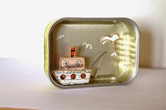 Bateau en découpe de papier collée sous du kraft armé dans un tableautin fait avec une boite de conserve de sardines - création Epistyle