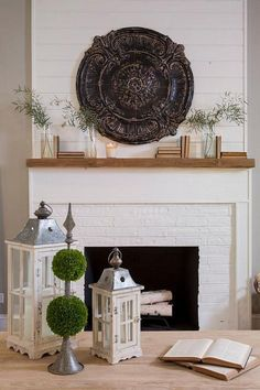 Shiplap wall above fireplace. Neutral Mantel Decor. Shiplap Fireplace Wall . This neutral fireplace mantel is dressed with French Country accessories, books and topiaries. #Fireplace #Mantel #Decor Via HGTV.