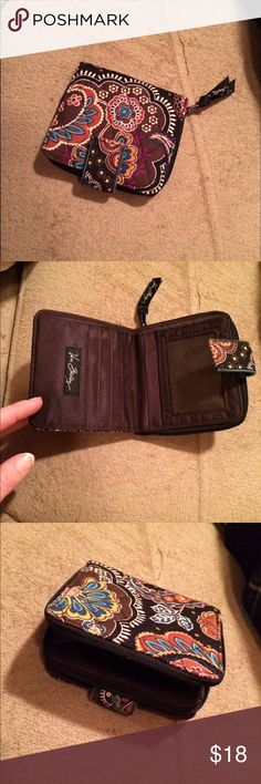 """Vera Bradley zip wallet Vera Bradley wallet. Snap closure with zipper coin partition. Amazing condition. Barely used. No rips, tears, pulls, discoloration, or fading.  Opening for bills inside. Credit card slots inside. Folds to a square shape. Gorgeous wallet with beautiful colors. Colors on this wallet: black, brown, rust, light and dark blue, white, goldenrod yellow, and magenta. When closed measurements are 4""""x4"""". Perfect size that opens and allows for bills to fit without being folded…"""