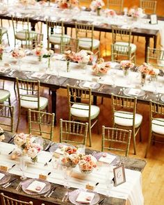 Long farm tables set with crystal charger plates, a mix of stemware and flatware, and distressed wooden chairs.