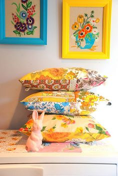 Embroidered artwork and bright pillows.