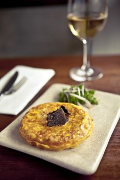 Tortilla con truffa. Racion or sharing plate of potato and onion tortilla served with shaved black Western Australian Truffle with parsley and spanish onion salad.