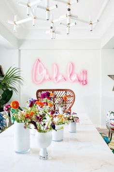 Oh la la wall neon light in marble kitchen with colour pops of flowers.