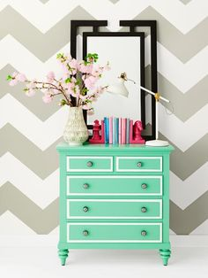 """With white trim and checkered knobs, a mint green dresser won't get lost against a mega-chevron wall. The drama continues with a black-framed mirror and bookends spray-painted feather boa pink. For tips on painting this design click here or go to hgtv.com/dresser-formula. Lamp: Ranarp 17""""-tall work lamp in off-white, $40, IKEA stores"""