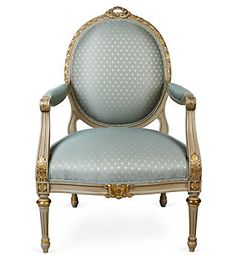 A Louis XVI fauteuil in pastel blue, common of Neo-Classical design, with a round back and gilded, carved detail.