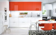 A kitchen with white and orange doors combined with white appliances, orange…