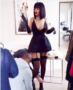 This the inspirational Rihanna wearing a short black Dior  dress , with a pair of classic lever Chanel gloves and a pair of thigh high stockings . She was getting ready for the spring fashion week in Paris . Later on that day she put on a red ,long length fur coat . That had sudden cut out at the shoulders .