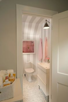 Tiffany Farha Design - Adorable pink and gray bathroom off of baby girls nursery featuring marble mini hex tiled floors and fun gray and white vertically striped walls. The bathroom features a modern white vanity paired with a bronze adjustable wall lamp. A Paule Marrot Feathers Acrylic Shadowbox Framed Print hangs over the modern toilet.