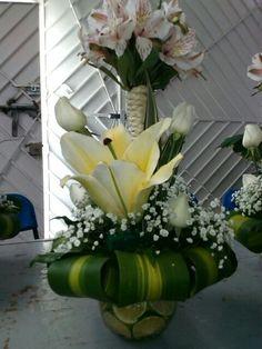 Atado de astromelia blanca con rosas blancas y flor de koncado en pecera de vidrio con rodajas de limon