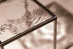 Sculpture/table acrylic glass 50 x 50 x 2 cm amplitude: max 3mm edition of 49 ©2010 Fredrik Skåtar Rack: aluminium frame 50 x 50 x 50 cm The wave table is a sculpture where the impact of a water dr…