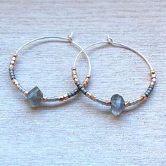 These Silver, Labradorite and Rose Gold 30mm Hoops were created by hand in London.The earrings are a noticable size at 30mm in diameter and are adorned in a very modern and elegantly edgy way, using sterling silver hoopd adorned with fair trade, faceted, 22 carat rose-gold vermeil along with assymetrically cut labradorite gem stones and grey glass beads. They can be worn day and night and look fab with floating layers as well as structured monocrome beige/white. They would make ...