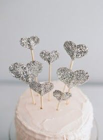 Easy to make cake toppers. Simply cut out different sized cardboard hearts, coat with a thin layer of PVA and dip into glitter. Leave to dry, and then using double sided tape, sandwich a kebab skewer between two hearts of the same side, simple yet effective!