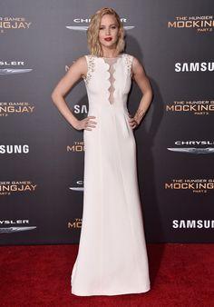 Jennifer Lawrence con vestido blanco largo con bordados dorados y transparencia en el centro del cuerpo, de Dior.