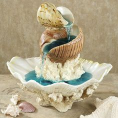 Shell Island Table Fountain- at touch of class.com $54.99 5 star reviews. add blue food coloring to water..Love It!