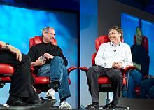 Steve Jobs & Bill Gates - Two men in their fifties shown full length sitting in red leather chairs smiling at each other