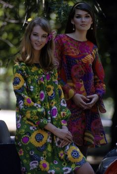 A pair of models, one in a green floral print dress and the other in a red paisley print dress, pose on a carriage in Central Park, New York City, August 1966. The photo was taken as part of a fashion shoot for Glamour Magazine.