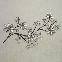 The contemporary Pearl Array Floral Metal Wall Art has a pristine beauty that gives any setting a refined, sophisticated air. Metal wall art features a branch finished in dark brown, adorned with florals in platinum and clusters of pearl buds. Wall art depicts a horizontal branch that makes a great decoration displayed alone or as a topper for your door, window, or other wall decor. 37