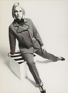 1968 Studio photograph of a female model wearing double breasted woollen jacket, with stripped detailing around the collar, cuffs and pockets, a stripped woollen turtleneck jumper, straight leg woollen trousers and black t-bar shoes. The model is seated on a small cube with split legs. The garments in the photograph were designed by Richard Charlupski and made by Edda Azzola of Ricardo Knitwear, Melbourne.