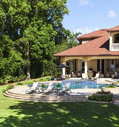 Here's another Spanish tile roof home, with an expansive patio spilling out from beneath a sheltered outdoor family room space. The pool boasts a raised water feature with waterfall.