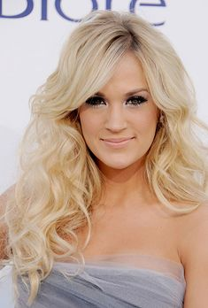 Long, Loose Curls Wedding Hairstyle. Country music star Carrie Underwood knows how to let her hair down. Here, her look is natural and romantic, yet sophisticated enough to pair with a designer wedding gown. (Underwood is known for favoring Reem Acra and Oscar de la Renta on the red carpet.) Browse more down wedding hairstyle ideas.  moreless