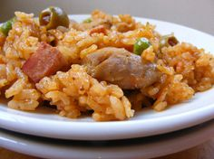 Puerto Rican Rice with Chicken – Arroz con Pollo Recipe Main Dishes with salt, black peppercorns, garlic, dried oregano, olive oil, lemon, chicken, olive oil, ham, beer, sofrito, tomato sauce, green olives, capers, achiote paste, white rice, chicken stock, peas, pimentos