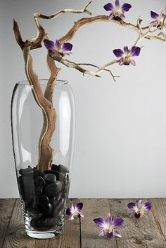 Elliptical Glass Vase with black river stones and a manzanita branch.