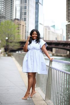 This model has a beautiful plus sized white and blue striped dress. With naked colored flats and a brown bag, this outfit is great for date nights or a casual walk in the park. Use a belt and tie it at the waist to give yourself more of a figure. Curvy Fashion, Plus Size Fashion, Womens Fashion, Work Fashion, Women's Fashion Dresses, Skirt Fashion, Peplum Dresses, Blouse Dress, Plus Size Dresses