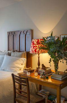 Decoração de apartamento clássico. No quarto de casal, cabeceira de madeira, abajur, plantas, adornos, quadros e roupa de cama branca.