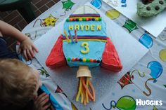 My son requested a rocket ship cake for his 3rd birthday. I baked a simple rectangle shaped cake and then cut the shape I wanted for the rocket and added some cut offs to make the wings. I dyed some basic vanilla buttercream to frost the cake. I used skittles, sour straps and silver cachous to decorate and an icecream cone and sour lollies from aldi for the flames at the bottom. I cut the name and number 3 out of dyed fondant using cookie cutters.