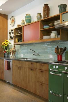 gorgeous kitchen: turquoise tile, green vintage stove, orange & wood cabinets, and red accents