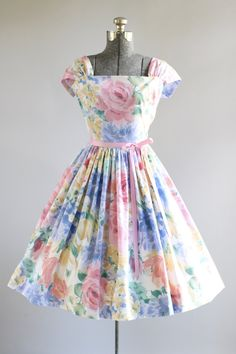 This 1980s does 1950s cotton dress features a beautiful floral print in shades of pink, blue and yellow. Ruched shoulder straps that can be worn off the shoulder. Nipped waist. Includes a pink ribbon waist tie (not original to the dress). Full pleated skirt. Nylon zipper up side of dress. Very good vintage condition. Please note: petticoat worn under skirt for added fullness. This piece has been cleaned and is ready to wear!  Label N/A Fabric Cotton Estimated Size M Tag Size N/A Pi...