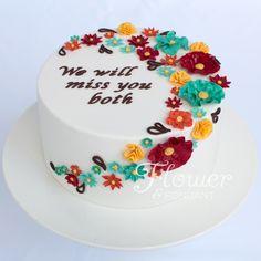 red, yellow, orange & aqua ruffle flowers on a farewell cake.
