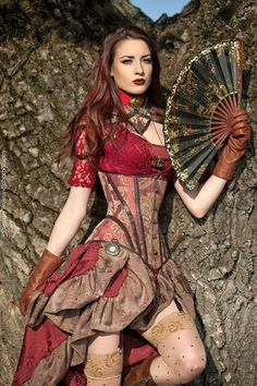 Steampunk in Burgundy Brocade (red lace blouse, tan and burgundy brocade underbust corset with matching skirt, polka dot thigh high stockings, brown gloves, necklaces, pocket watch and collar, and folding fan - For costume tutorials, clothing guide, fashion inspiration photo gallery, calendar of Steampunk events, & more, visit SteampunkFashionGuide.com