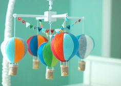 Five hot air balloons baby crib mobile.  Five different colors (white, blues, red, orange, gray and greens) hot air balloons and two rows of colorful bunting flags. You can also choose your own colors, just message me or leave your colors in the notes to the seller when placing your order. I would love to make something to fit your nursery! If no colors are chosen, I will make the mobile just like the photo. The balloons are made of wool felt and filled with hypo allergenic fiberfill…