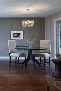 A beaded chandelier adds a refined touch of texture to this simple, serene dining area and echoes the shape of the round dining table.