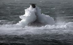 Storm waves crash over the Longships Lighthouse just off Lands End
